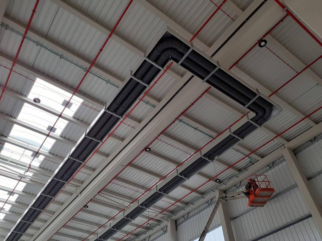 Tubos de calefacción radiante colgados sobre el teche de una nave industrial del grupo García Camarero.